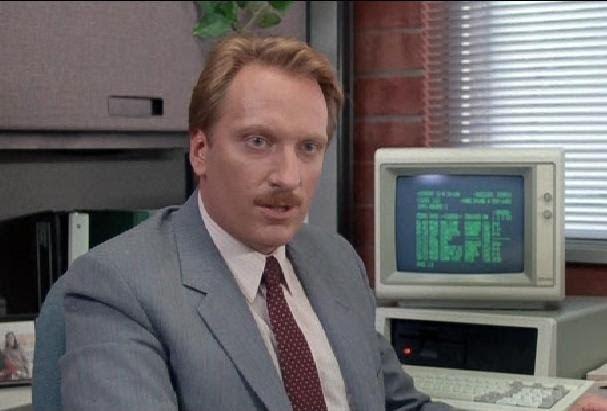 A movie scene of Jeffrey Jones as Ed Rooney wearing a gray suit in Ferris Bueller's Day Off (1986)