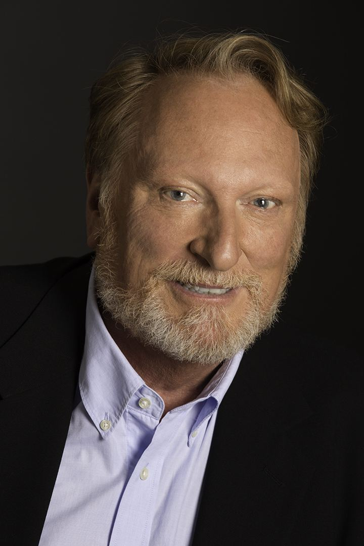 Jeffrey Jones smiles in the black background while wearing a black  suit and white long sleeve