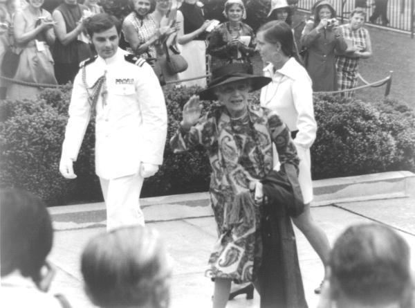 Alice Roosevelt Longworth wearing a dress and a hat with her granddaughter Joanna Sturm wearing a white dress escorted by the White House Social Aide at the crowd.