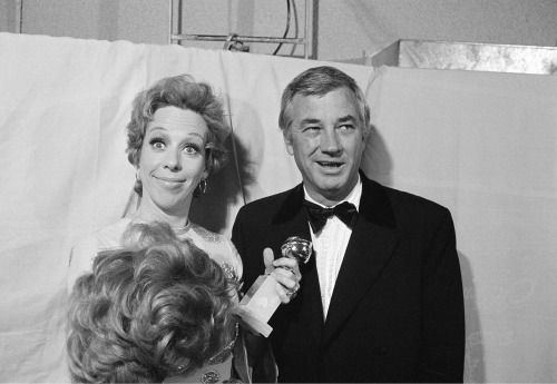 """Carol Burnett, accompanied by her husband and producer Joe Hamilton, is seen clowning backstage, holding her Golden Globe in one hand and a wig in the other, at the Golden Globe Awards in Los Angeles on February 6, 1971. Burnett received the award in the category of """"Best Television Show, Musical or Comedy"""""""