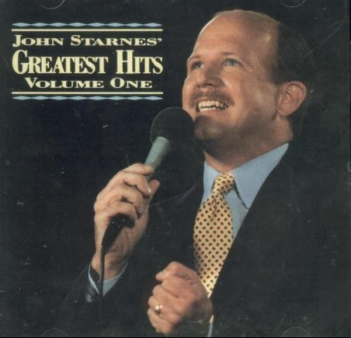 John Starnes wearing a black coat, blue long sleeves and red and yellow neck tie on his Greatest Hits Volume 1