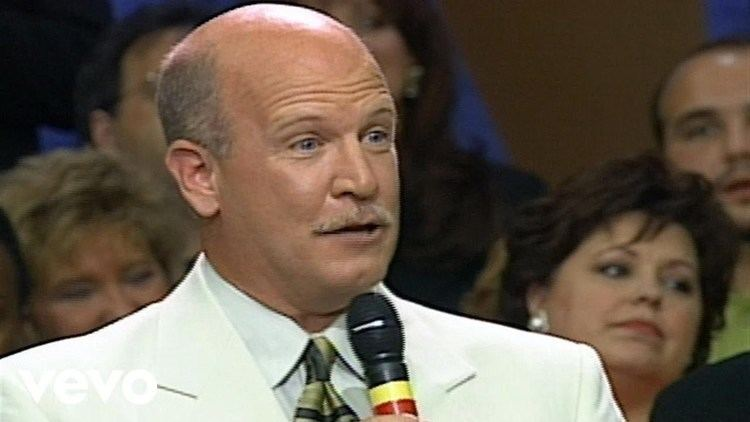 John Starnes in his white coat and white long sleeves while holding a microphone