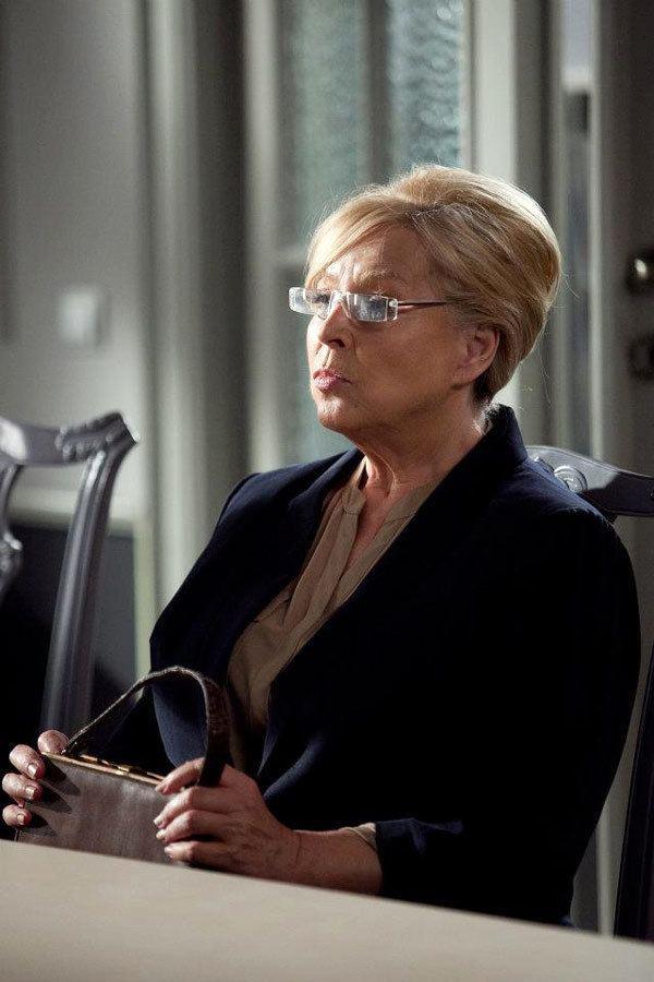 Jolanta Lothe wearing a black coat and eyeglasses while holding her bag