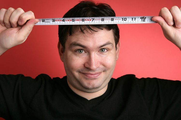 Jonah Falcon wearing black t-shirt while smiling and holding meter stick