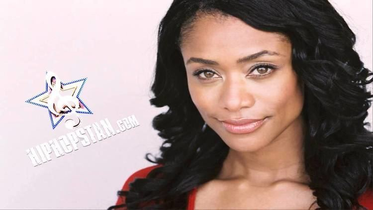 Tami Roman, ex-wife of Kenny Anderson, wearing a red shirt with black curly hair.