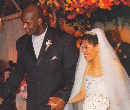 Kenny Anderson wearing a suit and his wife wearing a white gown holding a bouquet of white flowers.