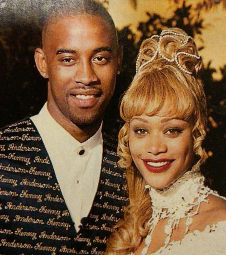 Kenny Anderson wearing a suit with his name on it and his wife wearing a white gown with red lipstick and blonde hair.