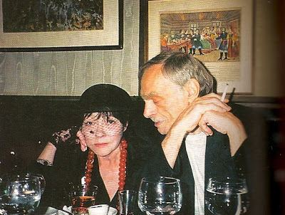 Lev Zbarsky looking at the woman beside him who is wearing black hat, black blouse and red necklace