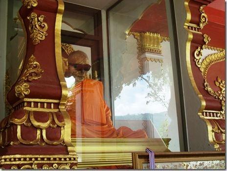 Luang Pho Daeng Monje Luang Pho Daeng sentado en una caja de cristal Tailandia