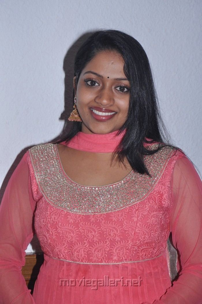 Mallika wearing earrings, a pink scarf, and a pink dress.