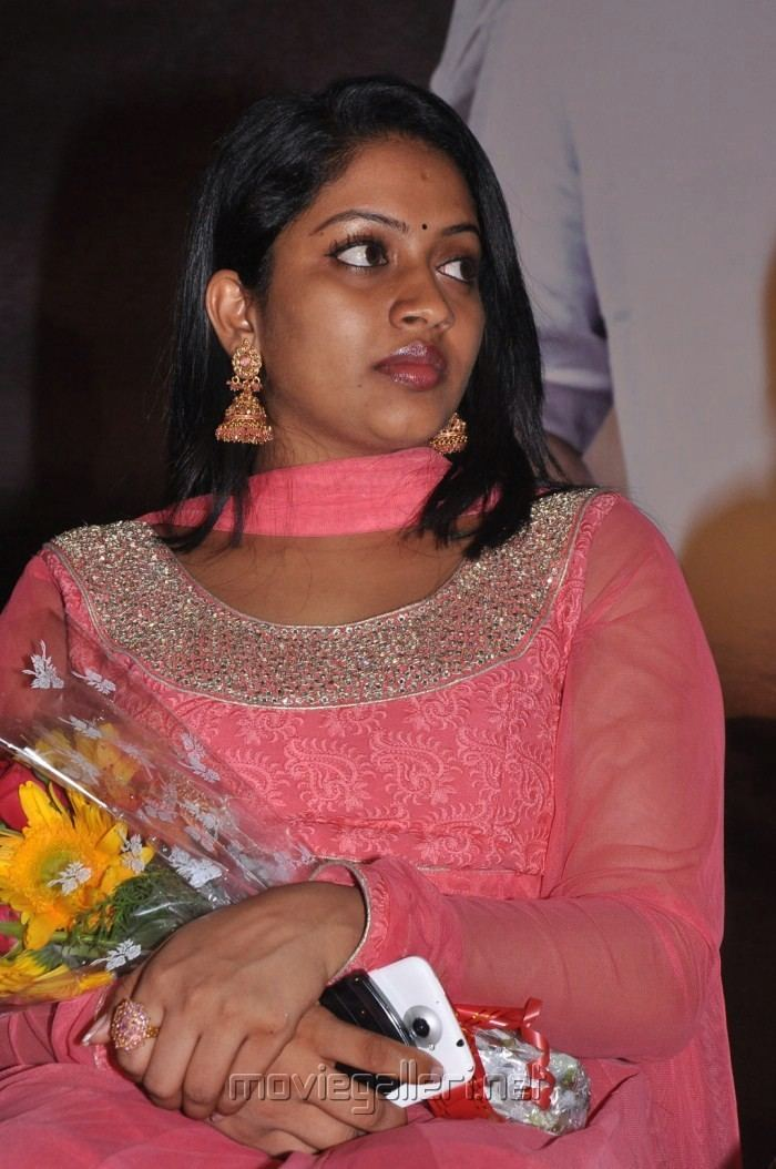 Mallika wearing earrings, a pink scarf, and a pink dress while holding a bouquet of flowers and a mobile phone.
