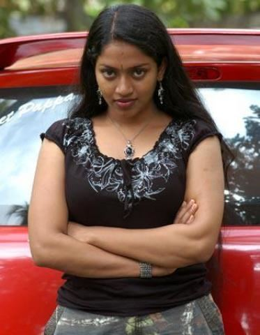 Mallika wearing earrings, a necklace, and a brown shirt beside a red car.