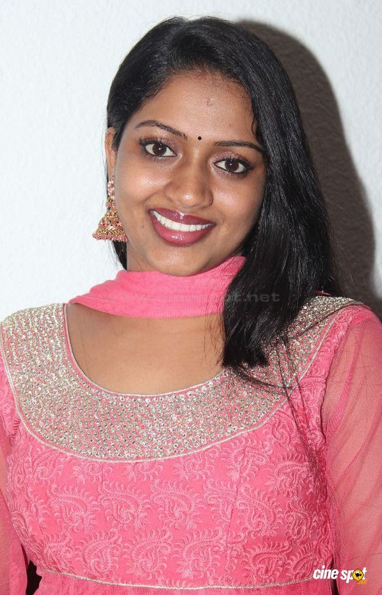 """Reeja Johnson, better known by her stage name """"Mallika"""", an Indian actress, wearing earrings, a pink scarf, and a pink dress."""