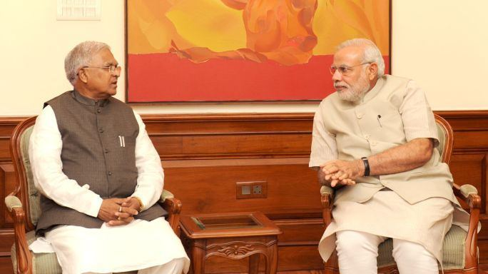 Mangubhai C. Patel with Narendra Modi sitting and talking to each other in the chair while wearing a formal attire
