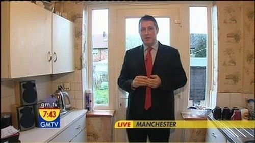 Matt Arnold as News Correspondent in GMTV television company, wearing a black suit and a red tie.