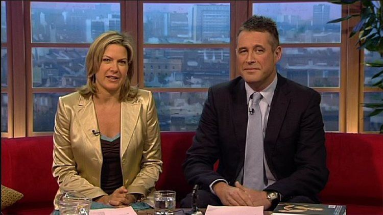 Matt Arnold wearing a black suit and a gray tie with a woman with blonde hair and wearing a yellow suit during a television show.