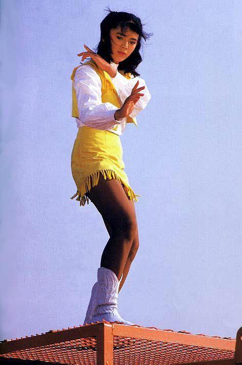 Naomi Morinaga wearing white and yellow tops, a yellow skirt, and white boots.