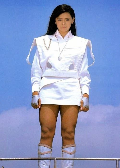 Naomi Morinaga wearing a necklace, a white top and skirt, and white boots.