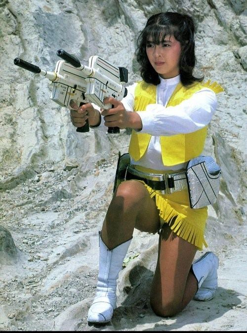 Naomi Morinaga holding guns, wearing white and yellow tops, a yellow skirt, and white boots.