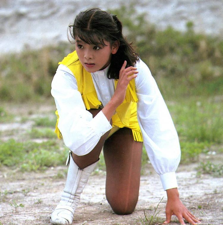 Naomi Morinaga with bangs, wearing white and yellow tops, a yellow skirt, and white boots while kneeling on the ground.