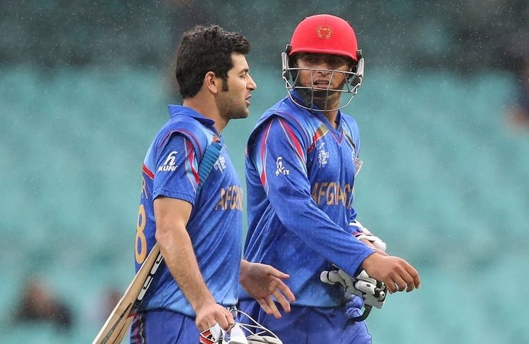 Nasir Jamal and Afsar Zazai walk back after rain interrupted play