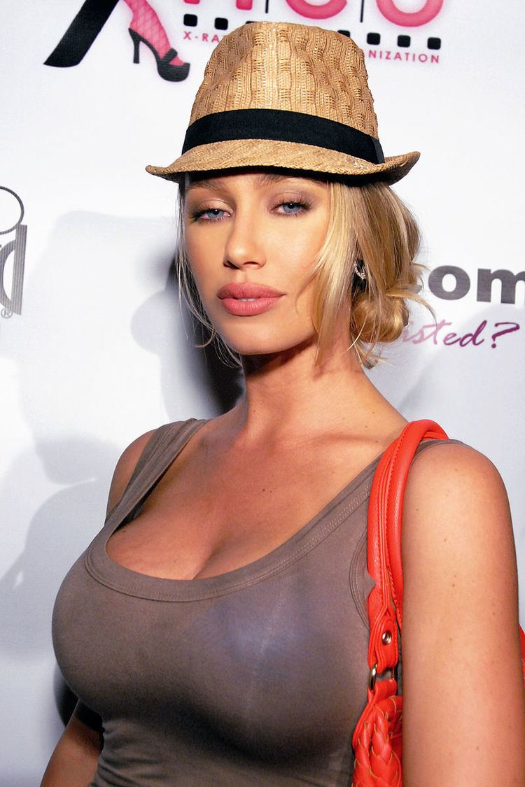Nicole Aniston with blonde hair, wearing a brown hat, gray sleeveless shirt with an orange bag.