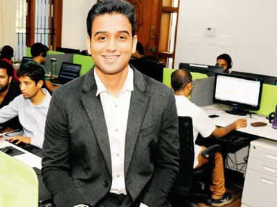 Nithin Kamath with a smiling face, wearing a black suit, and a white shirt with people at his back on their computers.