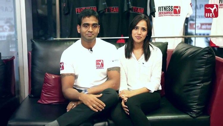 Nithin Kamath wearing a white polo shirt, a watch, rings, and black pants with his wife, Seema Patil wearing white long sleeves, a ring, and black pants, both are sitting on a black couch with shirts on their back.