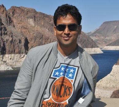 Nithin Kamath at Hoover Dam, wearing sunglasses, a gray jacket, and a gray shirt printed with a ball and stars.