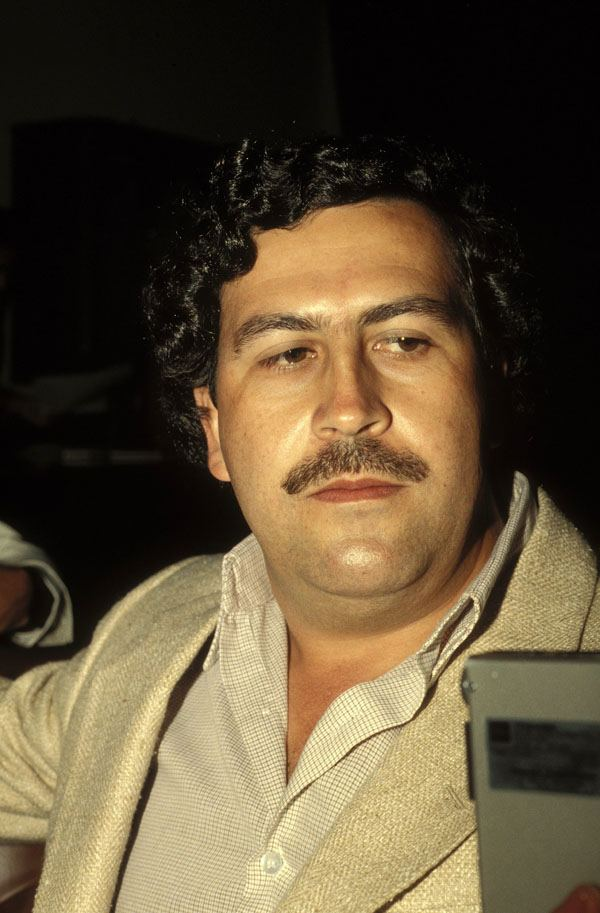 Pablo Emilio Escobar Gaviria with a mustache, curly hair, and wearing a suit.