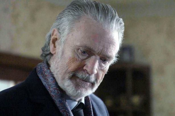 Patrick Bergin wearing black coat, long sleeves and black neck tie