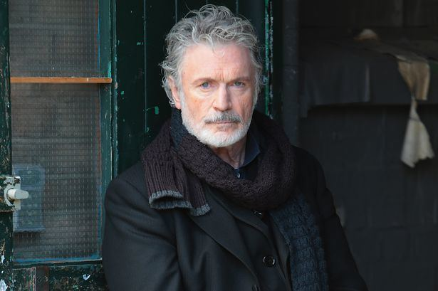 Patrick Bergin with gray hair and wearing black scarf and black coat