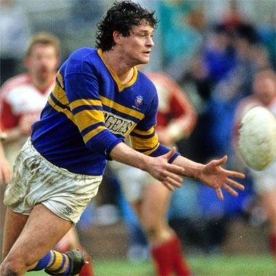 Peter Jackson playing rugby while wearing a blue and yellow top and white shorts