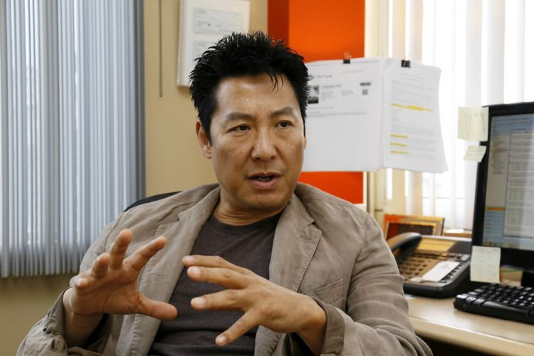 Phillip Rhee talking to someone while wearing a brown jacket and black shirt