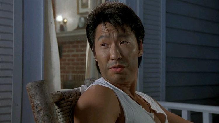 Phillip Rhee sitting on the chair while wearing a white sando
