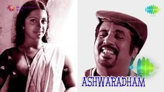 On the left, Srividya smiling and wearing a dress and necklace while, on the right, Raveendran smiling and wearing a hat