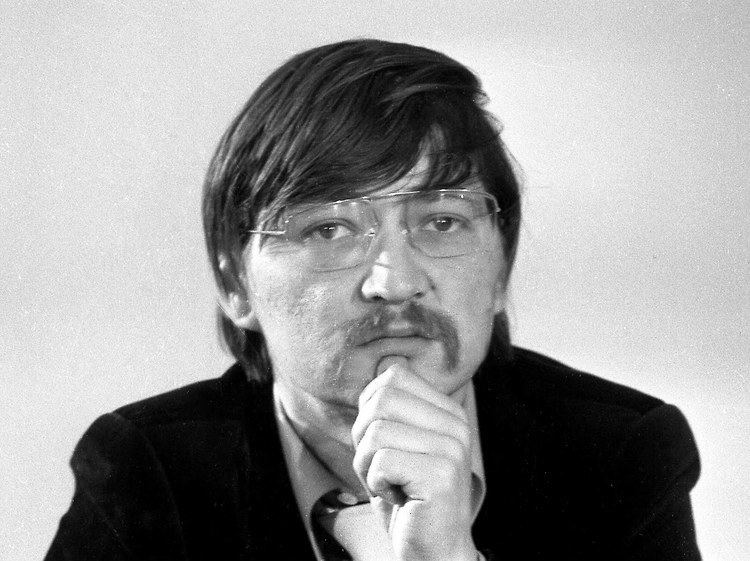 Rainer Werner wearing a black suit and a pair of eyeglasses