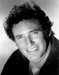 Robert Brown smiling while wearing a jacket and turtle neck