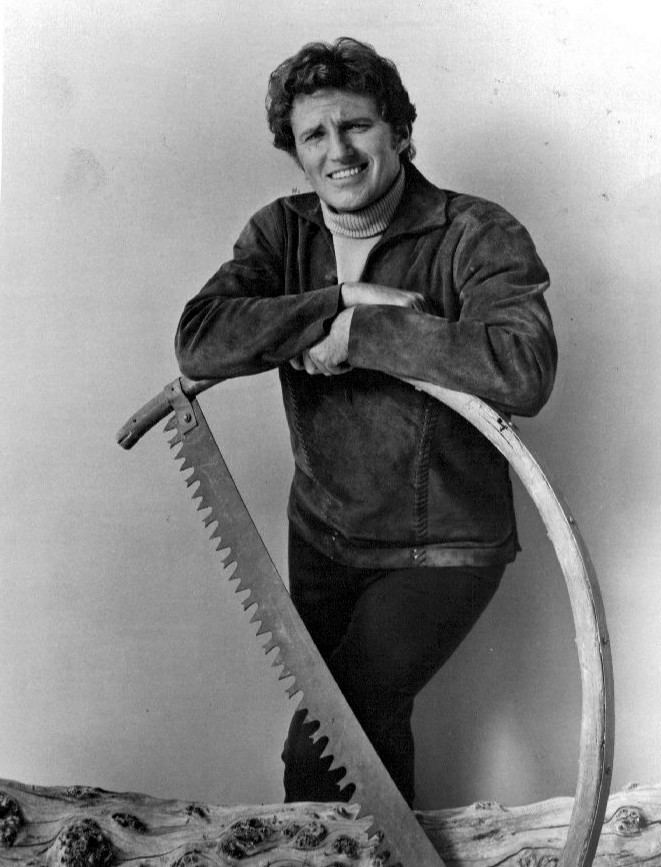 Robert Brown smiling and leaning on a big saw while wearing a jacket, turtle neck and pants
