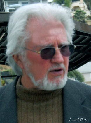 Robert Brown with a beard is wearing a gray coat and brown inner shirt