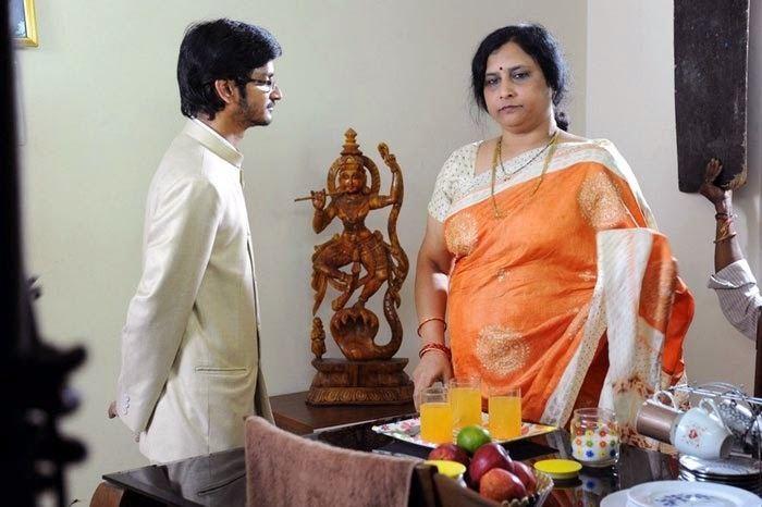 Roja Ramani wearing white and orange dress and the man beside him wearing white long sleeves