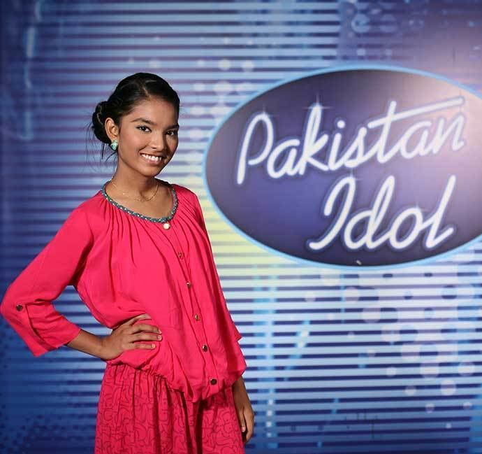Rose Mary wearing earrings, a necklace, and a pink dress in Pakistan Idol.