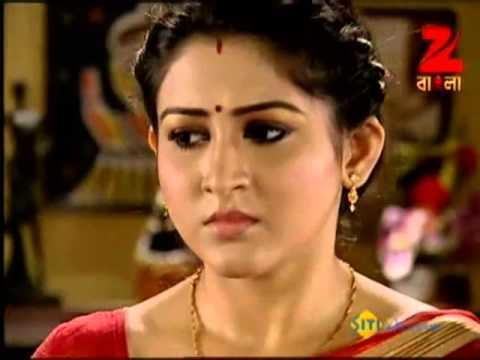 Oindrila Sen wearing red dress and gold jewelries in a scene from the 2009 movie, Saat Paake Bandha