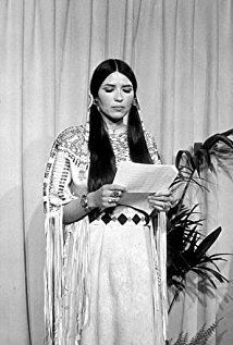 Sacheen Littlefeather wearing dress and jewelries while looking at the piece of paper she holds