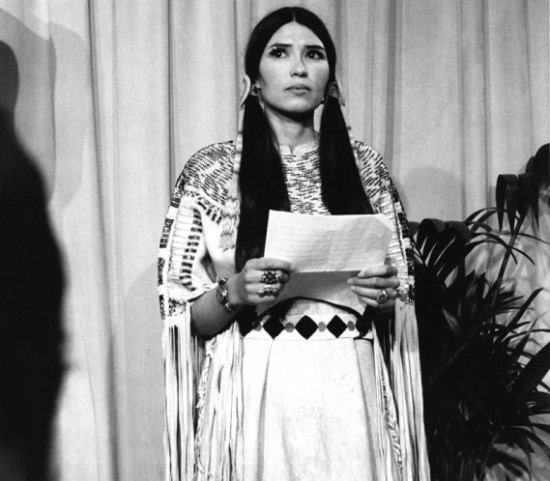 Sacheen Littlefeather wearing dress and jewelries while holding a piece of paper
