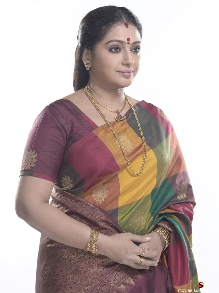 Seetha wearing earrings, a gold necklace, bangles, rings, and a Sari dress.