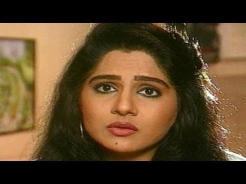 Shagufta Ali with a sad face, curly black hair, and wearing earrings.