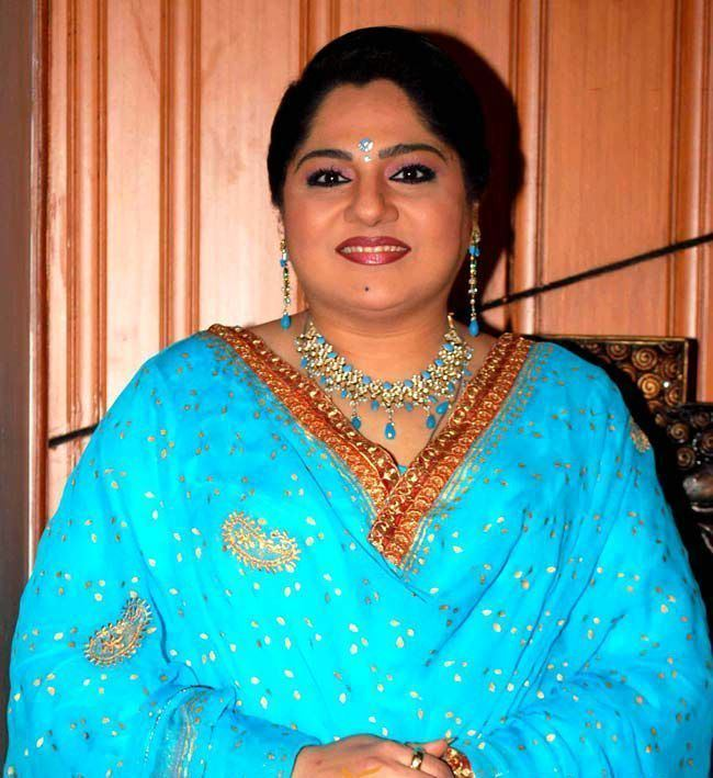 Shagufta Ali smiling, wearing earrings, a necklace, and a blue dress.
