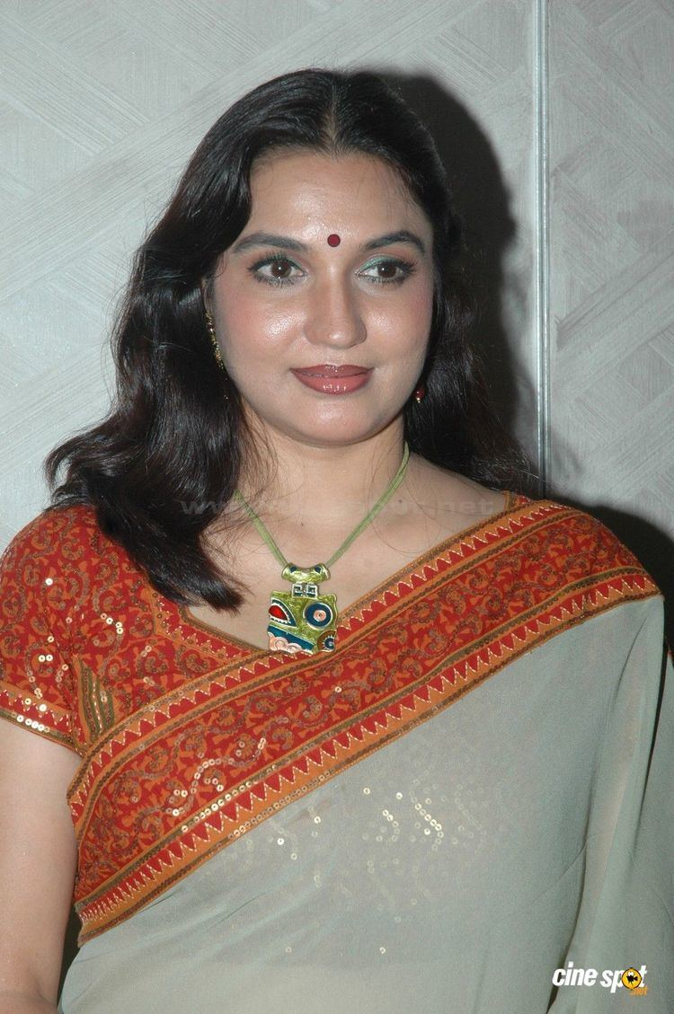 Sukanya wearing earrings, a necklace, and an orange dress.