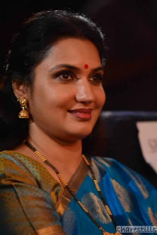 Sukanya wearing earrings, a necklace, bracelets, and color blue and yellow dress.
